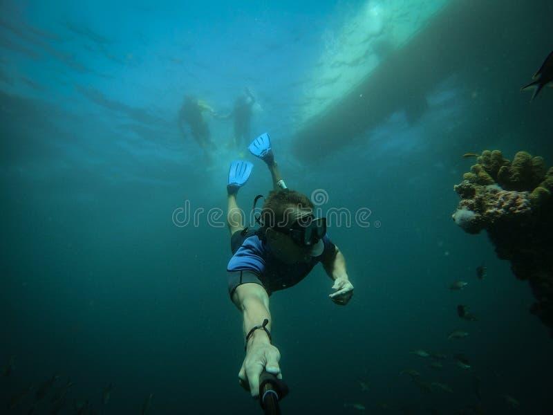 Vrije duiker die selfie met gedaald schip op achtergrond nemen stock foto's