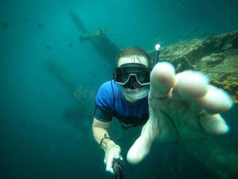 Vrije duiker die selfie met gedaald schip op achtergrond nemen stock afbeelding