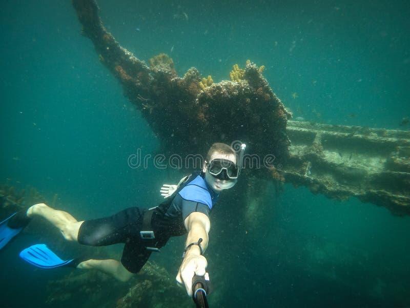 Vrije duiker die selfie met gedaald schip op achtergrond nemen stock fotografie