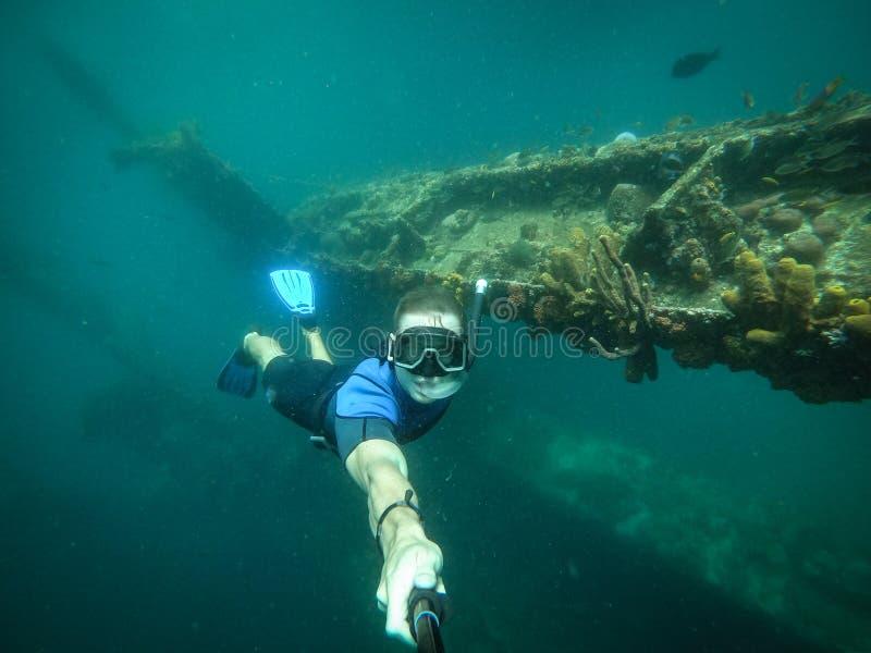 Vrije duiker die selfie met gedaald schip op achtergrond nemen royalty-vrije stock foto