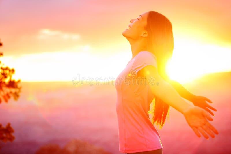 Vrije gelukkige vrouw die aard van zonsondergang genieten royalty-vrije stock afbeelding