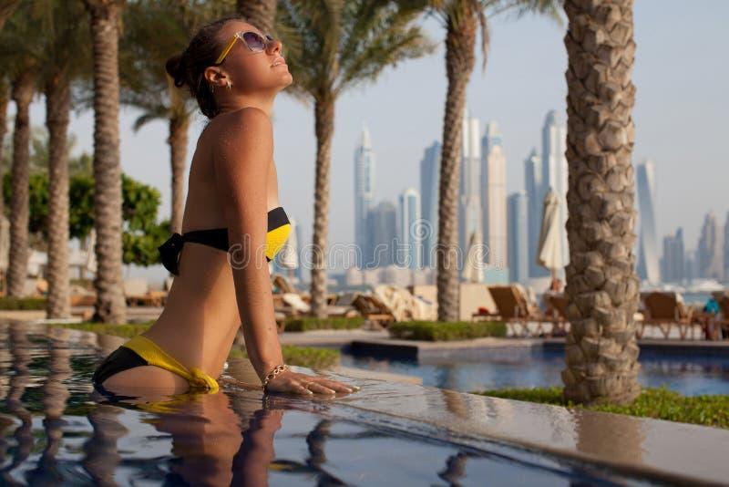 Vrije gelukkige vrouw die van zonsondergang genieten, die bij de luxe ontspannen poolsid stock afbeelding