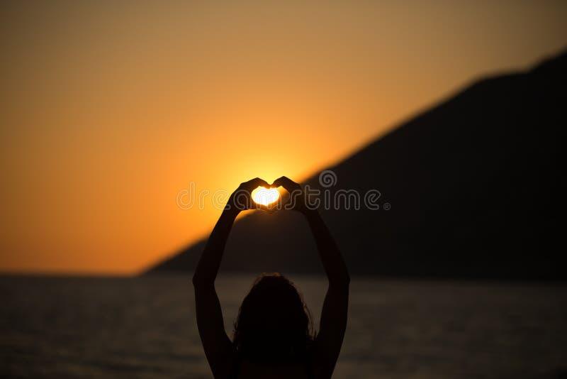 Vrije gelukkige vrouw die van zonsondergang genieten Omhelzend de gouden zonneschijngloed die van zonsondergang, van vrede, seren royalty-vrije stock foto
