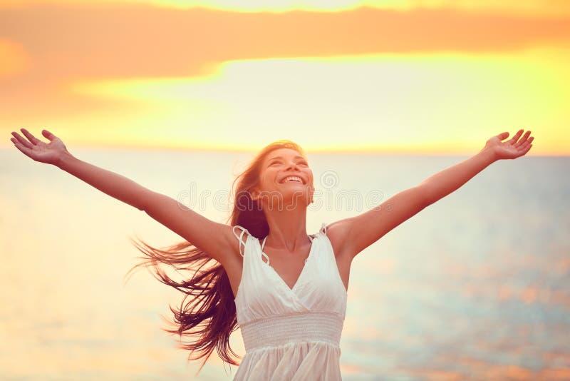 Vrije gelukkige vrouw die vrijheid prijzen bij strandzonsondergang stock afbeelding
