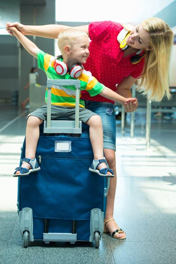 Vrije tijd bij de luchthaven De moeder en weinig zoon wachten op zijn vlucht royalty-vrije stock afbeelding