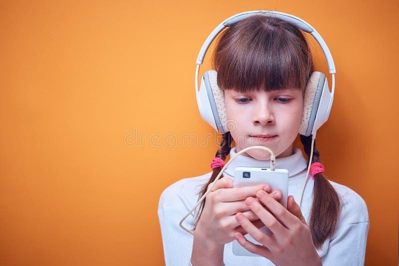 Vrije tijd en vermaak, Kaukasisch tienermeisje die aan muziek met hoofdtelefoons luisteren die de telefoon op gekleurd met behulp royalty-vrije stock afbeelding