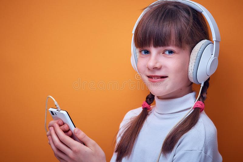 Vrije tijd en vermaak, Kaukasisch tienermeisje die aan muziek met hoofdtelefoons luisteren die de telefoon op gekleurd met behulp stock afbeeldingen