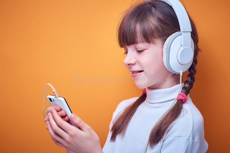 Vrije tijd en vermaak, Kaukasisch tienermeisje die aan muziek met hoofdtelefoons luisteren die de telefoon op gekleurd met behulp stock afbeelding