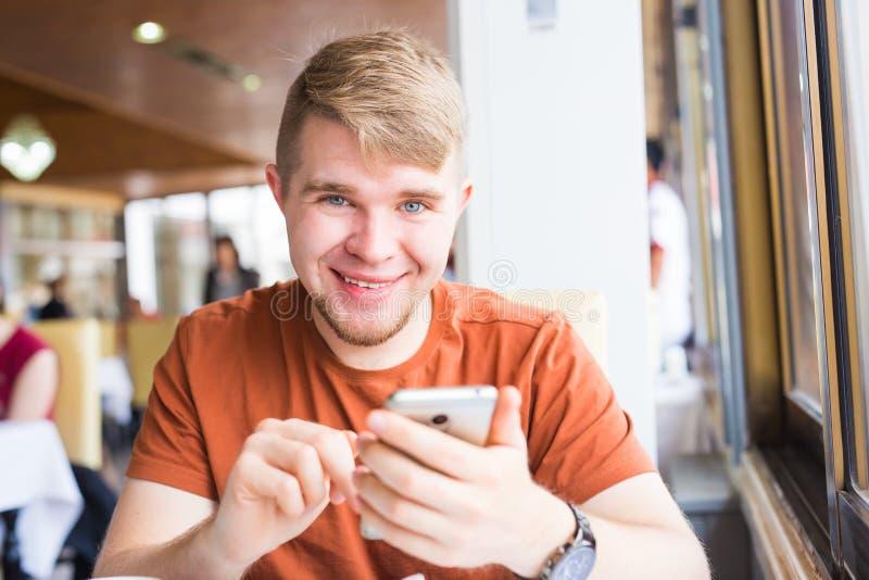 Vrije tijd, technologie, mededeling en mensenconcept - sluit omhoog van de mens met smartphone texting bericht in stadskoffie royalty-vrije stock afbeelding