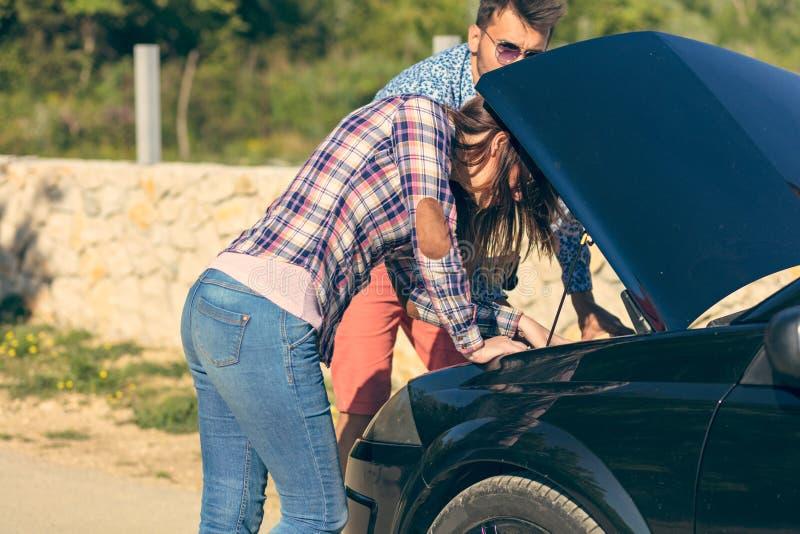Vrije tijd, wegreis, reis en mensenconcept - gelukkige vrienden die gebroken cabriolet auto langs landweg duwen stock afbeelding