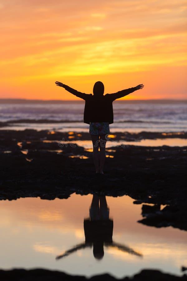 Vrije vrouw die van vrijheid op strand genieten bij zonsondergang stock afbeelding