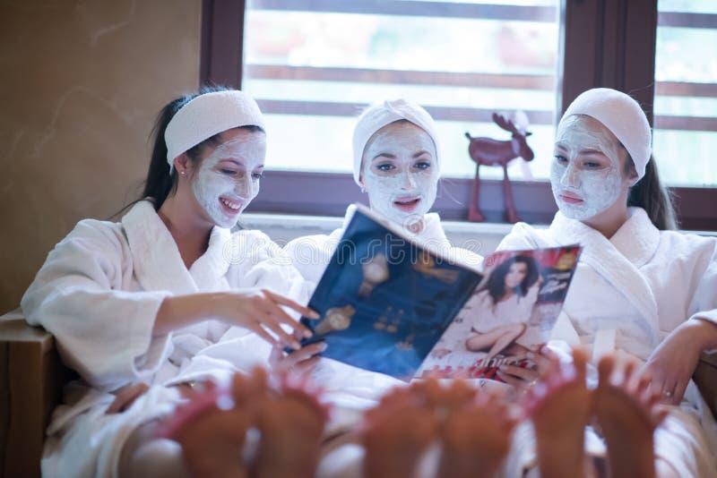 Download Vrijgezellinpartij In Kuuroord, Meisjes Met De Lezingstijdschrift  Van Het Gezichtsmasker Stock Afbeelding   Afbeelding