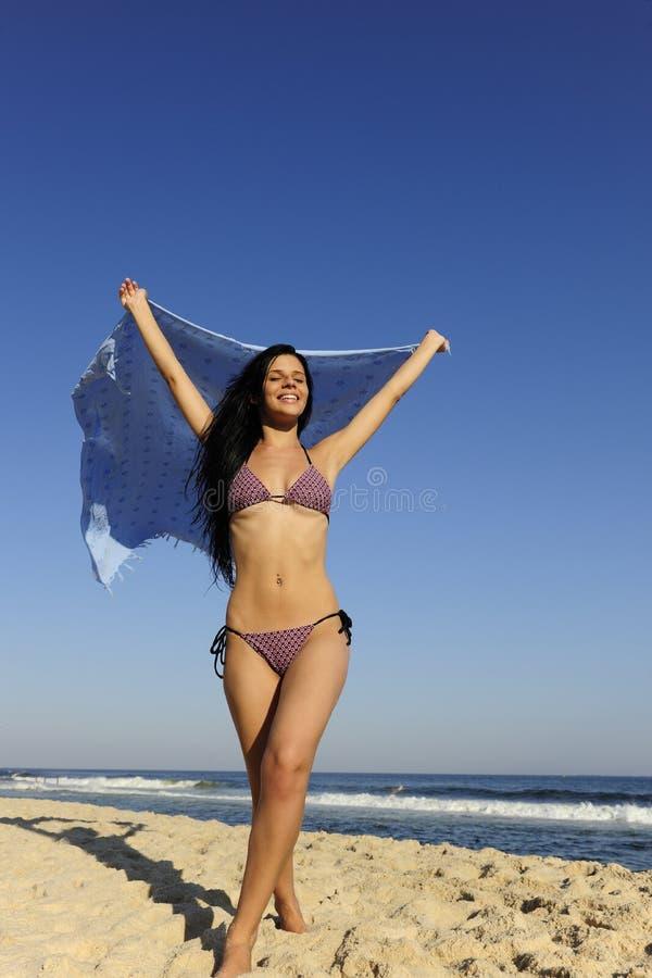 Vrijheid: vrouw met strandhanddoek tegen blauwe hemel royalty-vrije stock afbeelding