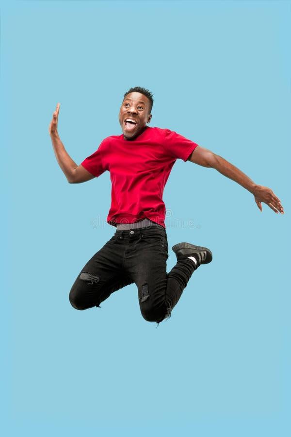 Vrijheid in zich het bewegen en voorwaartse motie Het gelukkige verraste jonge afromens springen stock foto