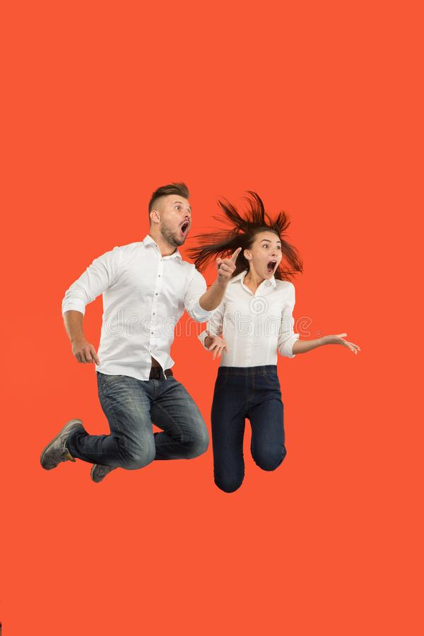 Vrijheid in zich het bewegen Verrast jong paar die tegen rode achtergrond springen stock foto
