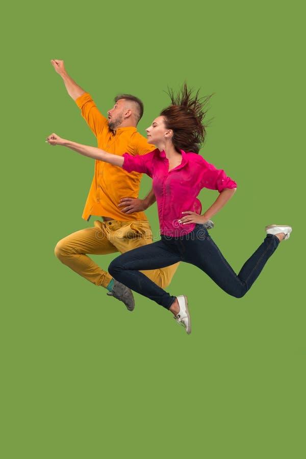 Vrijheid in zich het bewegen Vrij jong paar die tegen groene achtergrond springen royalty-vrije stock foto's