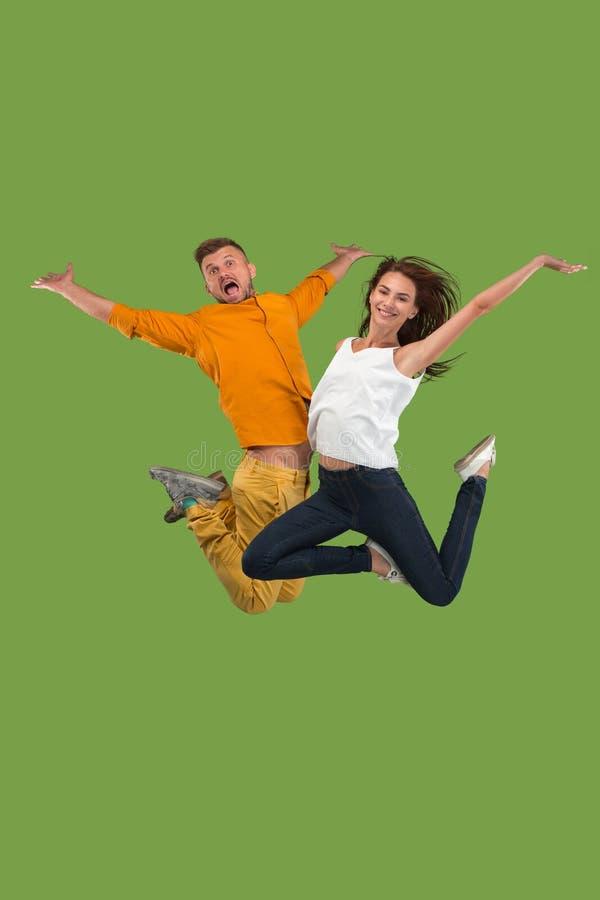 Vrijheid in zich het bewegen Vrij jong paar die tegen groene achtergrond springen royalty-vrije stock afbeelding