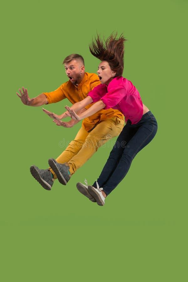 Vrijheid in zich het bewegen Vrij jong paar die tegen groene achtergrond springen stock foto