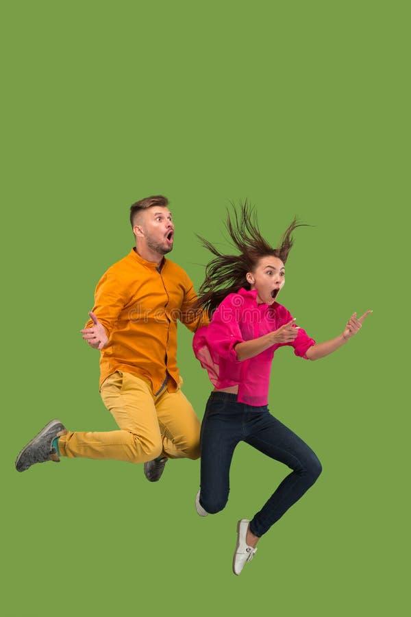 Vrijheid in zich het bewegen Vrij jong paar die tegen groene achtergrond springen stock afbeelding
