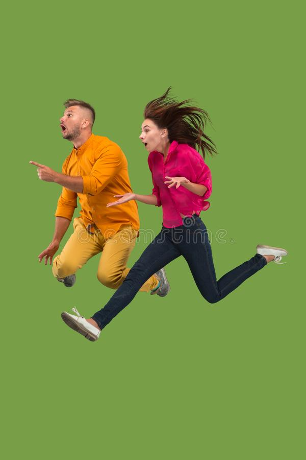 Vrijheid in zich het bewegen Vrij jong paar die tegen groene achtergrond springen royalty-vrije stock afbeeldingen