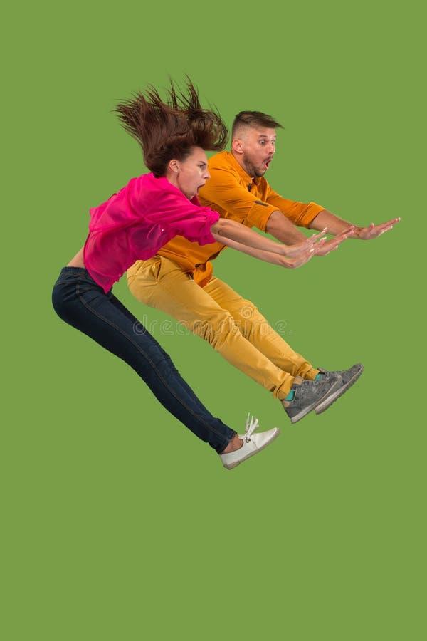 Vrijheid in zich het bewegen Vrij jong paar die tegen groene achtergrond springen royalty-vrije stock foto