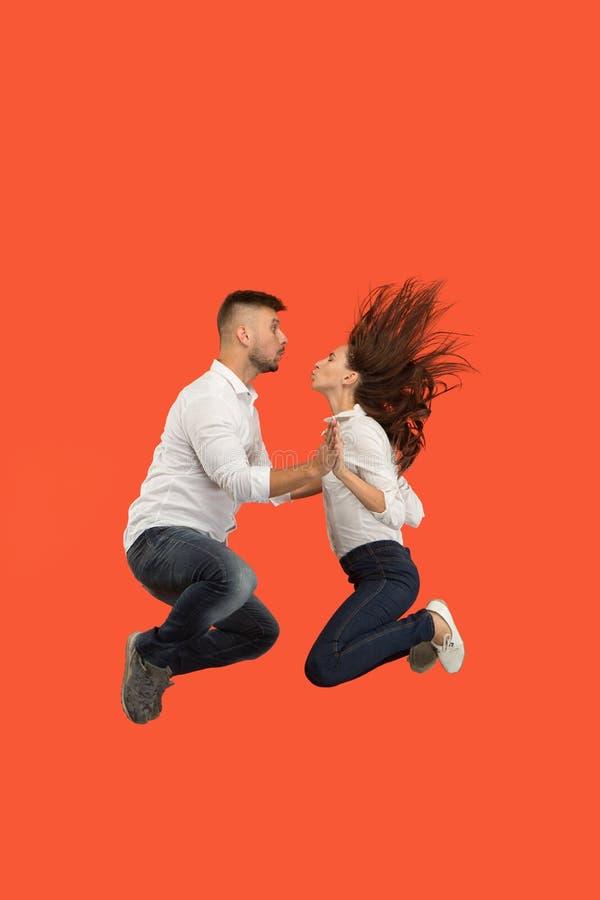 Vrijheid in zich het bewegen Vrij jong paar die tegen rode achtergrond springen stock fotografie
