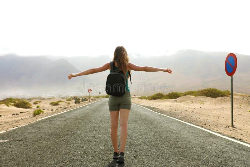 Vrijheids vliegende vrouw in vrije gelukzaligheid in de lege weg van de asfaltwoestijn Gelukkige vrouwelijke reiziger die backpac royalty-vrije stock afbeeldingen
