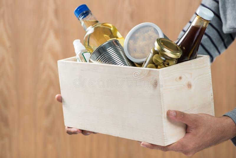 Vrijwilliger met schenkingsdoos met voedselmaterialen op houten backgroun stock afbeelding