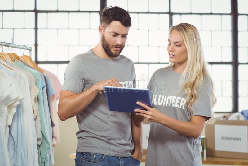 Vrijwilligers die digitale tablet gebruiken stock afbeelding