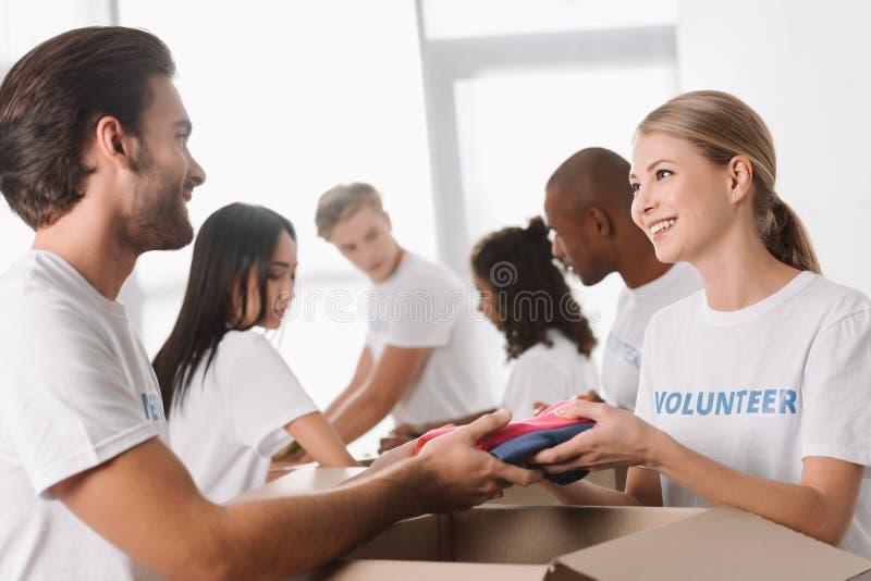 Vrijwilligers die kleren voor liefdadigheid inpakken stock fotografie
