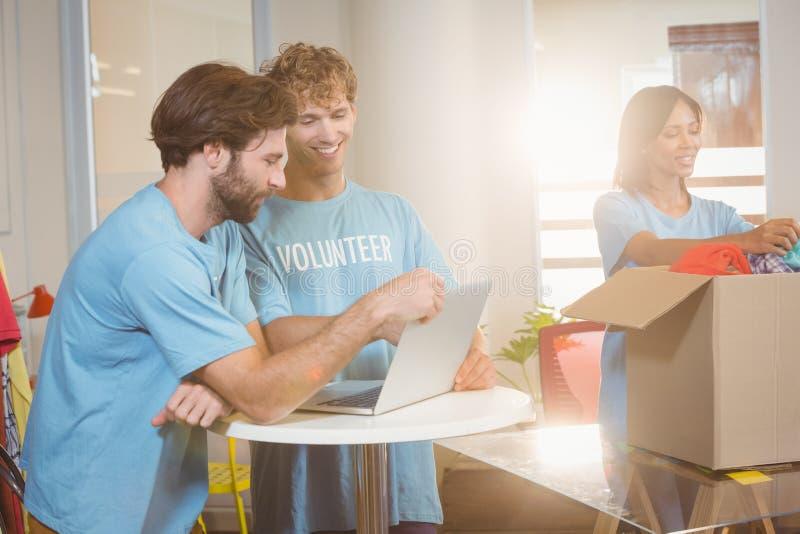 Vrijwilligers die laptop met behulp van stock fotografie