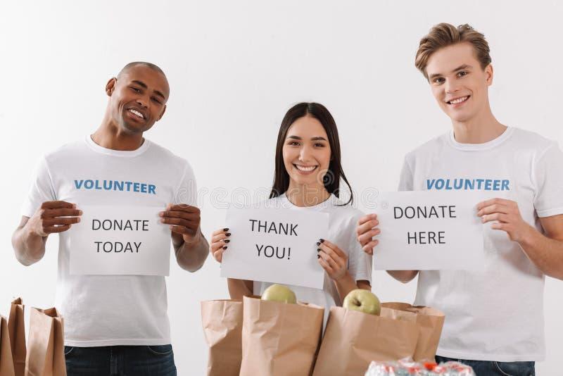 Vrijwilligers die liefdadigheidsaanplakbiljetten houden royalty-vrije stock foto's