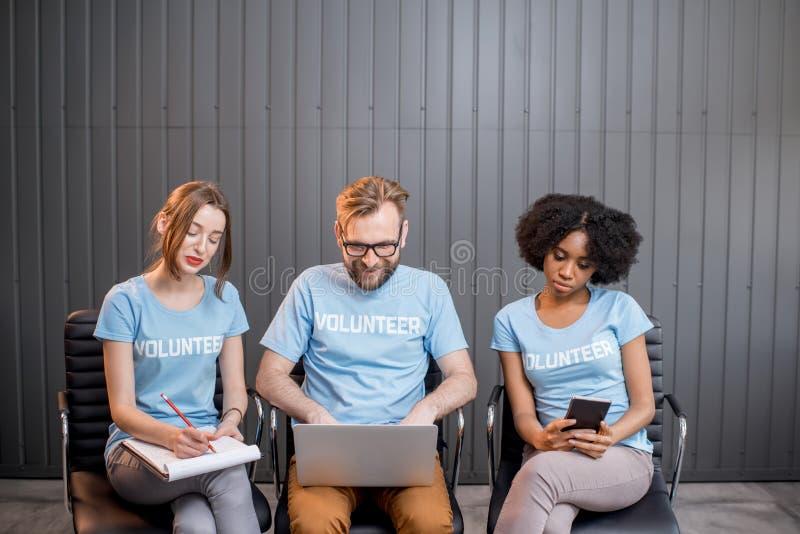 Vrijwilligers die op het kantoor werken stock foto's