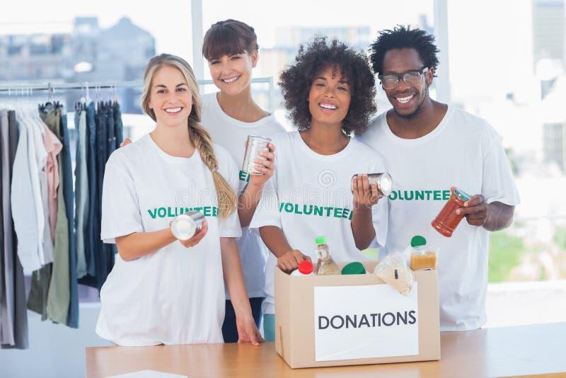 Vrijwilligers die voedsel van een schenkingsdoos nemen stock afbeeldingen