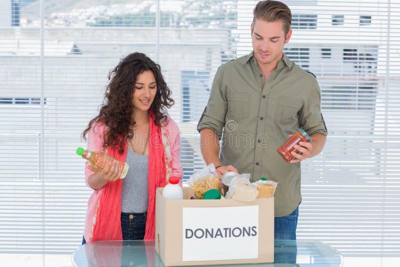 Vrijwilligers die voedsel van schenkingendoos nemen royalty-vrije stock fotografie