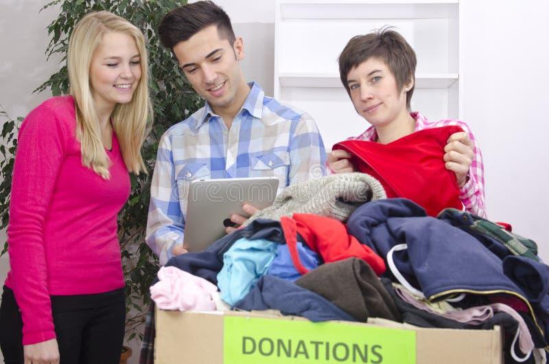 Vrijwilligers groep met kledingsschenking stock afbeelding