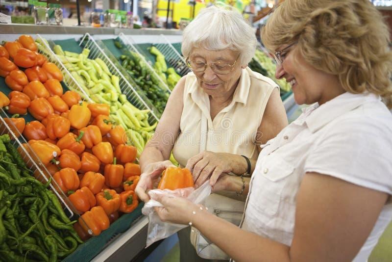 Vrijwilligers helpende oudste met haar die winkelt royalty-vrije stock afbeeldingen