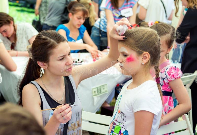 Vrijwilligers het schilderen kattenmasker op een meisjes` s gezicht royalty-vrije stock afbeelding