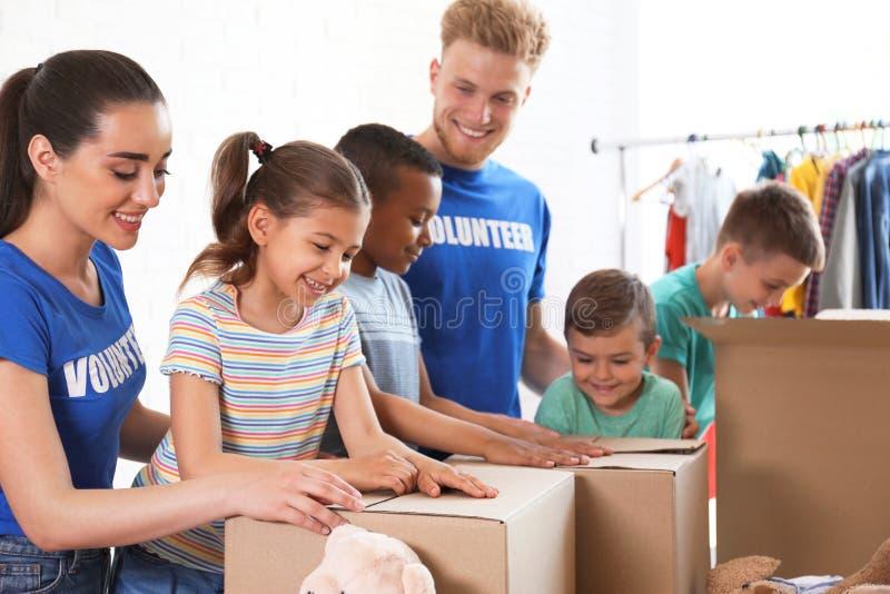Vrijwilligers met de goederen van de kinderenschenking binnen stock foto's