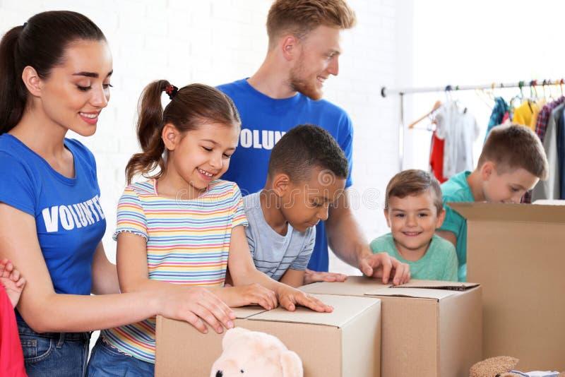 Vrijwilligers met kinderen die goederen binnen sorteren royalty-vrije stock foto