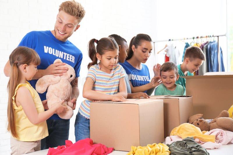 Vrijwilligers met kinderen die schenkingsgoederen sorteren royalty-vrije stock afbeeldingen