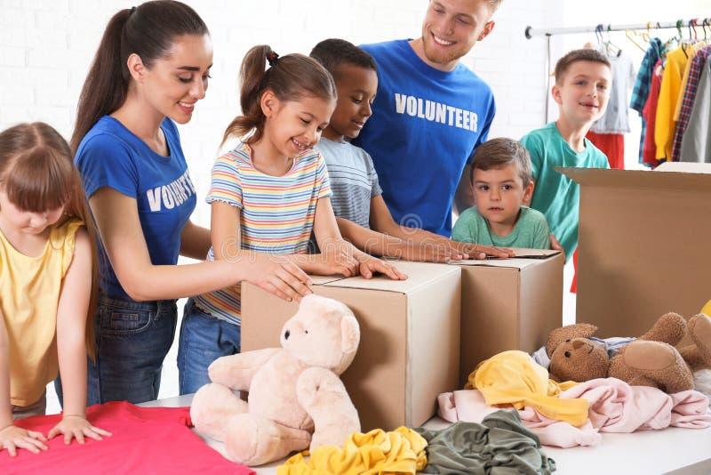 Vrijwilligers met kinderen die schenkingsgoederen sorteren stock afbeelding