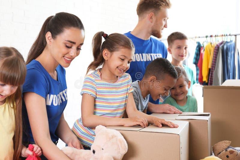 Vrijwilligers met kinderen die schenkingsgoederen sorteren royalty-vrije stock fotografie