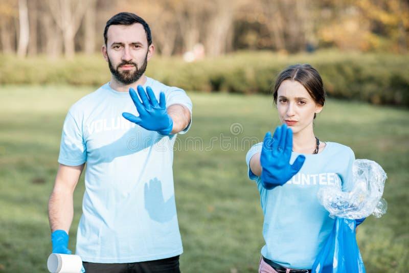 Vrijwilligers met vuilniszakken die einde met handen tonen royalty-vrije stock afbeeldingen