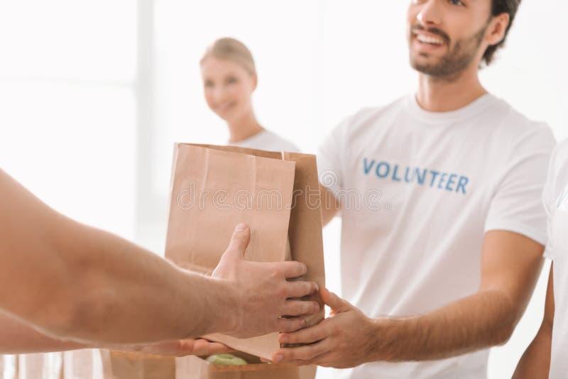Vrijwilligers nemend liefdadigheidspakket stock fotografie
