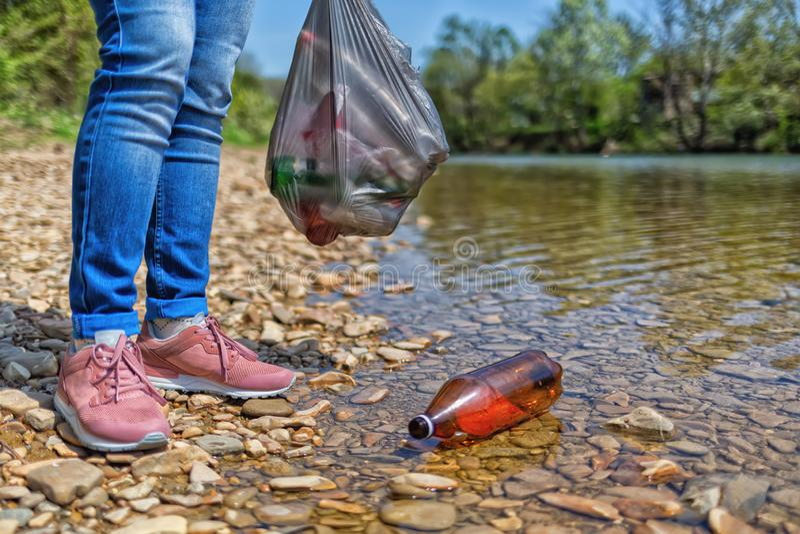 Vrijwilligers status op de Bank van de rivier, en het drijven in de rivier plastic fles Concept de bescherming van stock afbeelding