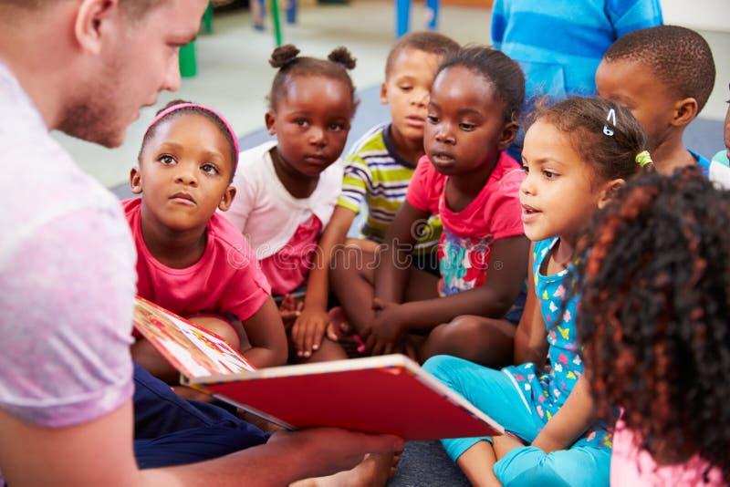 Vrijwilligersleraar die aan een klasse van peuterjonge geitjes lezen stock afbeelding