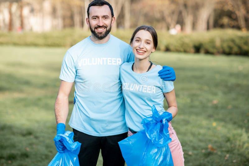 Vrijwilligersportret met vuilniszakken in het park stock foto