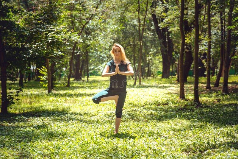 Vrikshasana Asanas de yoga en nature Le yoga pose quotidien Jeune femme de pratique Yoga en stationnement photos stock