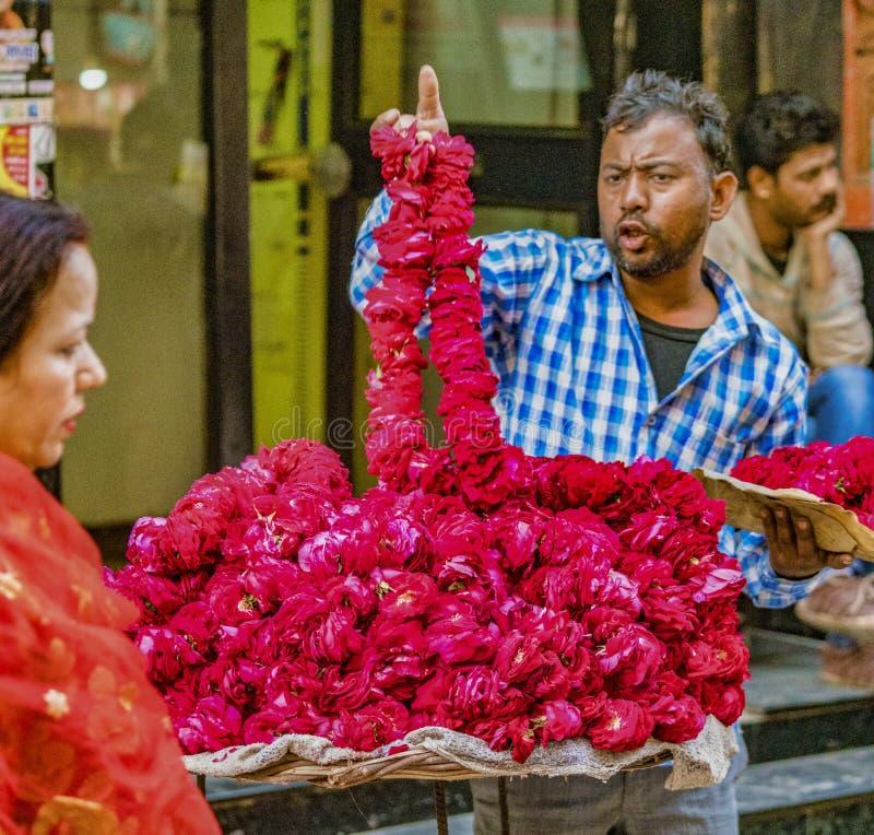 Vrindavan, la India/22 de febrero de 2018 - el hombre vende las guirnaldas rojas de la flor de su tabla de la calle fotos de archivo